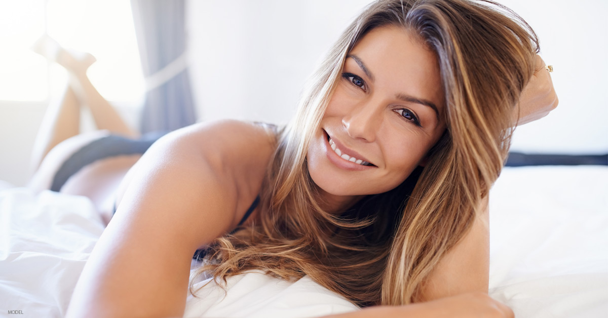 Woman lying on bed considering plastic surgery