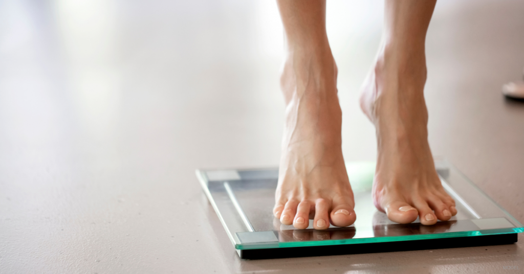 Woman standing on scale to check for weight gain after tummy tuck