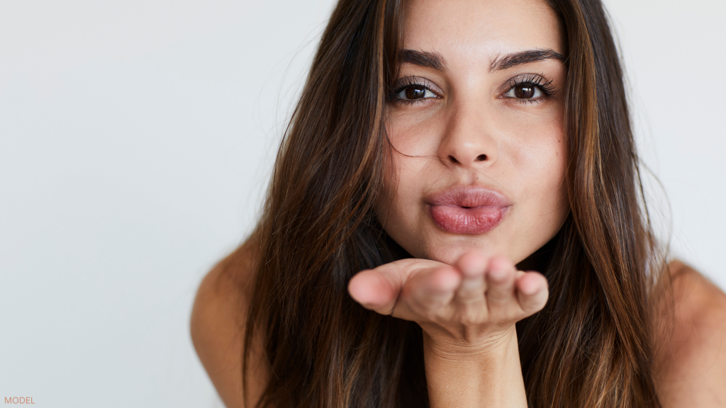 Woman showing off benefits of lip filler treatment in Annandale, VA and Chevy Chase, MD.